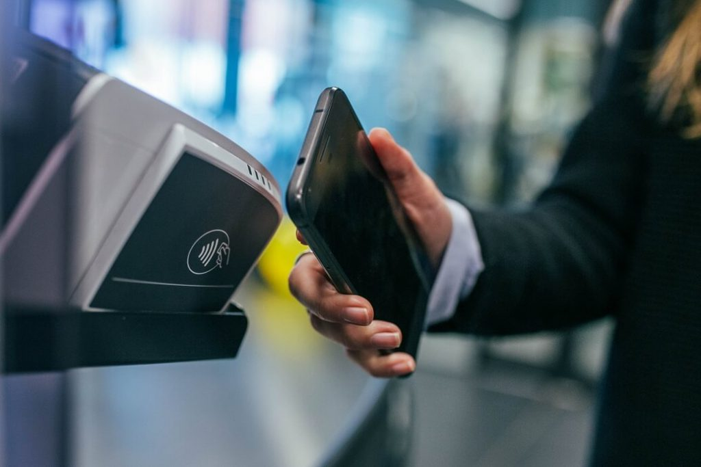 NFC Integration Company - Lady holding phone to pay using NFC